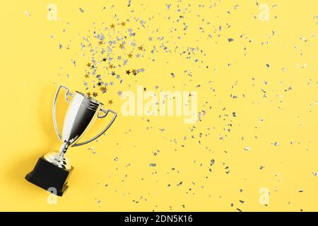 Winner or champion silver trophy cup on yellow background top view.  Winning or success concept. Stock Photo