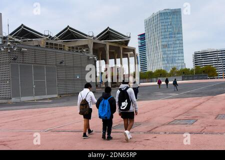Rear view of students with backpack walking. Parc del Forum, Barcelona, Catalonia, Spain.