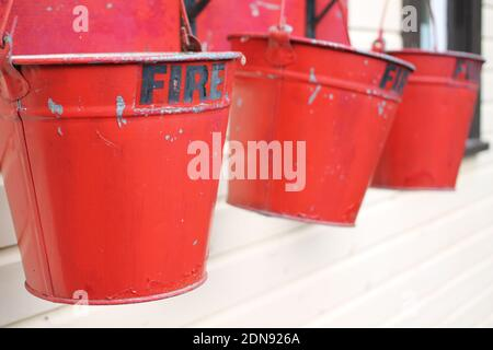 Close-up Of Red Metal Buckets With Fire Text Hanging Against Wall