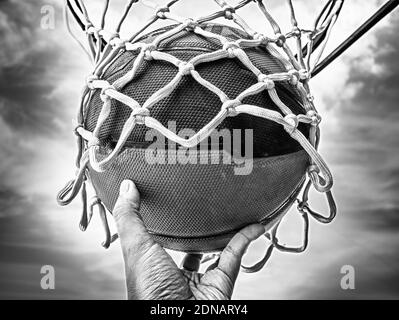 Cropped Hand Holding Ball In Basketball Hoop