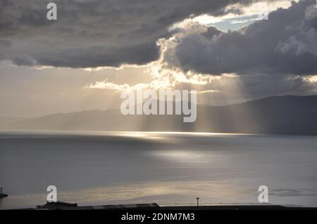 Sun rays passing through clouds on the sea.Dramatic cloudscape over sea.Dramatic sunset over sea. Sunbeams passing through clouds.