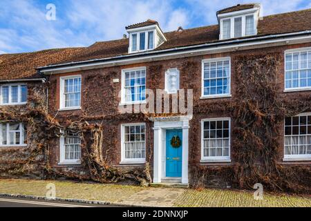 Georgian style terraced cottage (Church Hill House) in Church Hill, Midhurst, West Sussex, in winter with a Christmas wreath on its blue front door