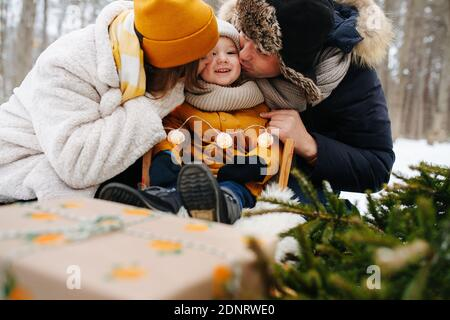 Happy parents kissing their little girl, sitting on a sleigh. In a winter forest
