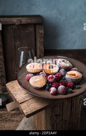 Still life with frozen berries and fruits in a brown plate on a vintage background.