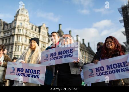 Protesters holding 'no more lockdowns' placards during COVID-19 anti-vaccine protest, Parliament Square, London, 14 December 2020 Stock Photo