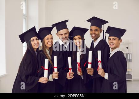 Portrait of a group of happy multiracial university graduates with diplomas in their hands.
