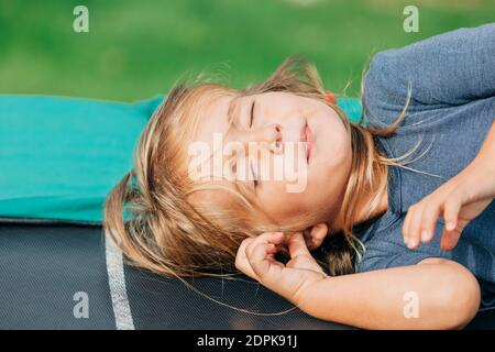 Toddler girl napping on trampoline – Kempen, NRW, Germany - Stock Photo