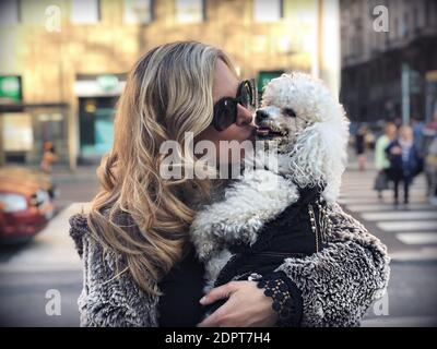 Woman Kissing Dog On Road In City