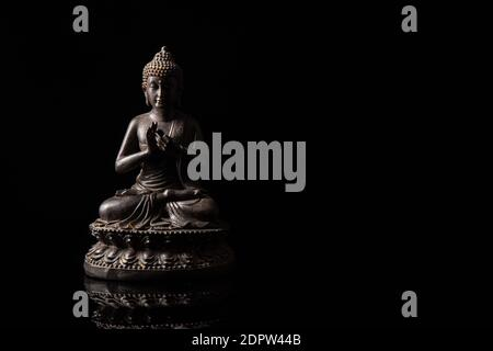 Statue of Buddha sitting in meditation With black copy space . Zen and meditation concept.