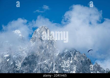 paragliding flies through the clouds over the rocky alps, the alps are covered with snow and clouds, the sky is blue Stock Photo