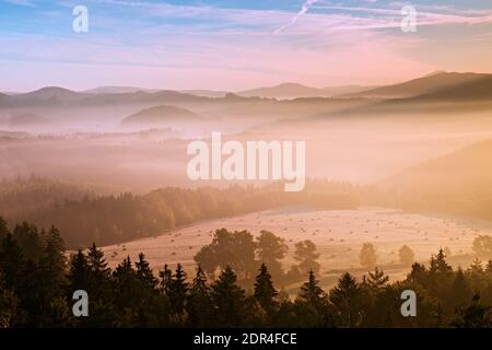 Pink daybreak in hilly landcape. Autumn misty morning in a beautiful hills. Peaks of hills are sticking out from fog Stock Photo