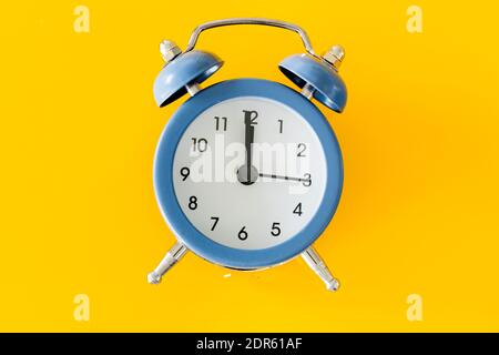 Stylish alarm clock showing five to twelve on a yellow background