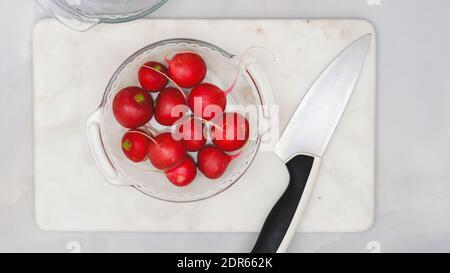 Fresh organic radish closeup on a plate on marble background , flat lay