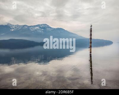 Mooring pole on lake como in a winter morning