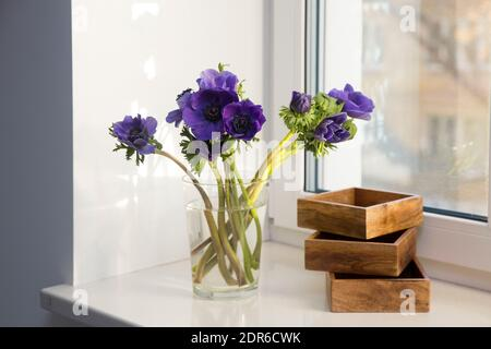 A bouquet of blue anemones in a glass vase next to three wooden boxes for storing small items on the windowsill. Copy space - Stock Photo