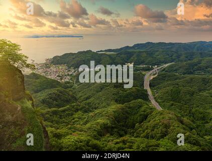 chiba, japan - july 18 2020: Sunset sky on the Uraga Channel and Kanaya fishing village with the Futtsu-Tateyama Road in the mountains of Boso peninsula from the cliff of the Mount Nokogiri quarry.