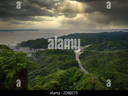 chiba, japan - july 18 2020: Sunlight filtering through a cloudy sky on the Uraga Channel and the Futtsu-Tateyama Road in the mountains of Boso peninsula from the cliff of the Mount Nokogiri quarry.