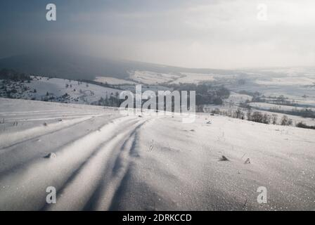Car tracks on snow with a mountain village in a distanse. Somewhere in the Carpathians.