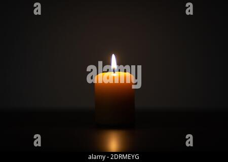 Yellow candle burning on dark background. Candle centered in the frame with empty space for text