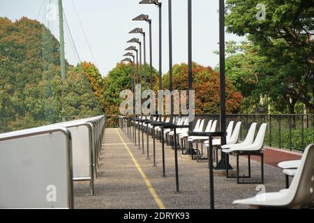 Empty Chairs On Footpath Against Trees