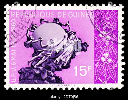 MOSCOW, RUSSIA - FEBRUARY 23, 2019: A stamp printed in Guinea shows Monument of the UPU, Berne, First anniversary of the approval of Guinea to the UPU - Stock Photo