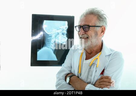 Portrait of senior doctor in hospital with x-ray film background. - Stock Photo