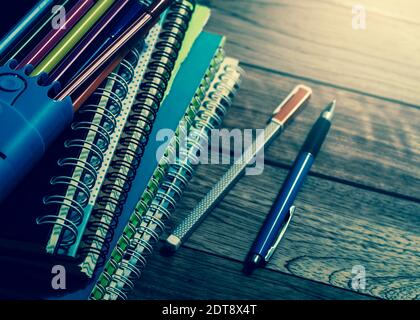 Heap of notebook with pens on wooden table under light in vintage style - Stock Photo