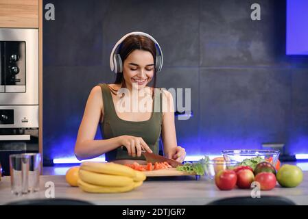 Healthy young woman cutting fruits and vegetables on a wooden board while making breakfast and listens to music in a kitchen.