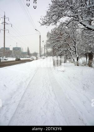 Sidewalk in winter covered with snow next to the roadway on which there is dirty snow and cars are driving - Stock Photo