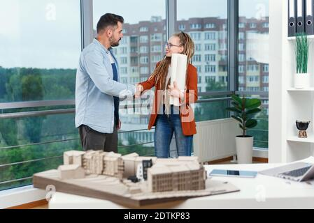 Pleasant experienced modern stylish satisfied young designers discussing work moments using blueprint with project of new buildings near panoramic win