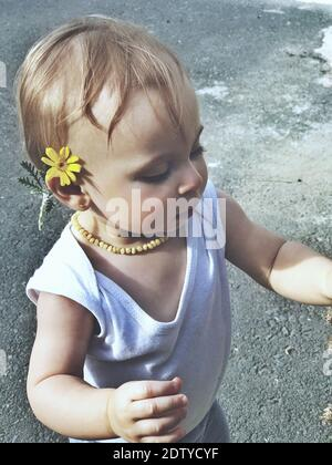 Close-up Of Cute Girl Wearing Flower While Standing On Road