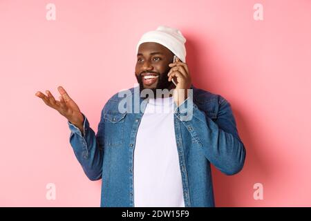Handsome modern african-american man talking on mobile phone, smiling and discussing something, standing over pink background