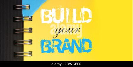 Build your brand text message words on yellow page of copybook in white and blue. Business startup concept.