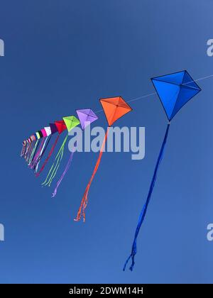Low Angle View Of Multi Colored Kites Flying Against Clear Blue Sky