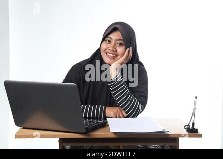 portrait of Asian woman wearing casual clothes working in an office. a veiled woman with a happy expression working at a computer. the concept of a su