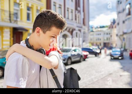 Meeting guy and teenage girl, hugging teenagers, street sunny summer city, copy space
