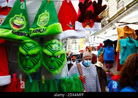 23rd December 2020, LA PAZ, BOLIVIA: A man wearing a face mask as protection against the covid 19 coronavirus walks past a street stall selling Grinch masks and hats in a Christmas market. - Stock Photo