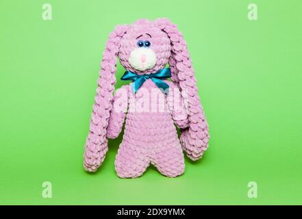 Toy pink bunny or hare on a green background - Stock Photo