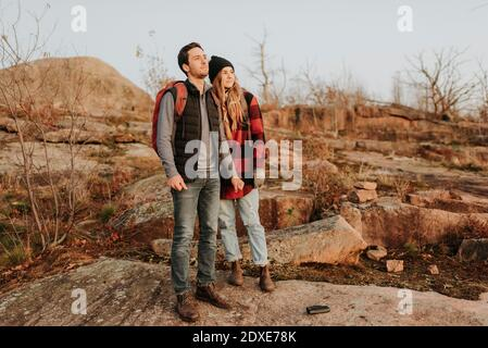 Young couple standing together and admiring surrounding landscape during autumn hike