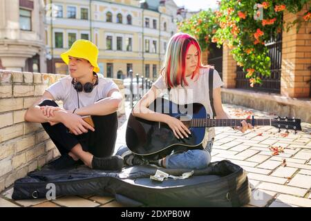 Couple of teenage hipsters street musicians making money by music