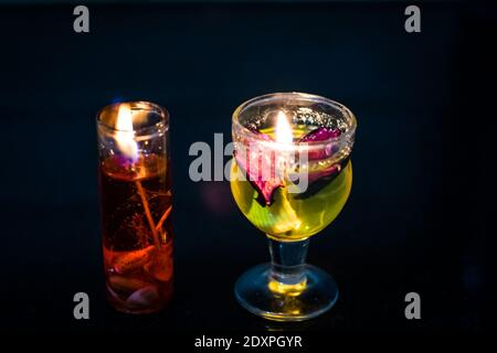 Close-up Of Multi Coloured Tea Light Candles On Table Against Black Background