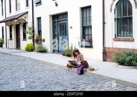 A woman reading from her computer on Washington Mews, a private gated street in Greenwich Village, Manhattan, New York City - Stock Photo