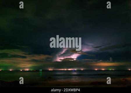 storm clouds in the sky over sea in night long exposure shot. - Stock Photo