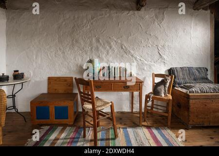 Front view of vintage room interior in traditional village country house. Old handmade furniture, school desk, wooden chairs, craft chest on stucco wa - Stock Photo
