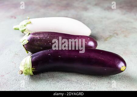 Raw purple and white eggplants or aubergines with water drop on green stone background. Selrctive focus. Stock Photo