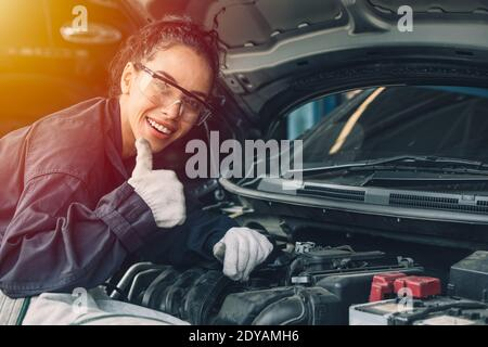 Portrait happy working woman work for auto mechanic job in garage hand thumbs up sign for good condition car engine