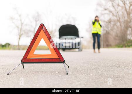 Young Caucasian woman, talking on her cell phone while her car is broken down on the road with reflective warning triangles. Selective focus. Automobi