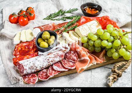 Italian antipasto, wooden cutting board with prosciutto, ham, parma, goat and Camembert cheese, olives, grapes. antipasti. Gray background. Top view