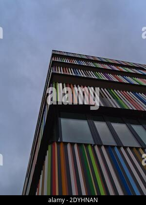 Low angle view of modern residential building with multi-colored balcony railing and windows on the facade on cloudy day.