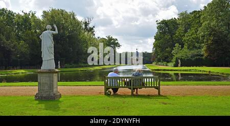 Couple sitting on bench overlooking the Thomas Archer pavillion and Long Canal at Wreat Park. Stock Photo